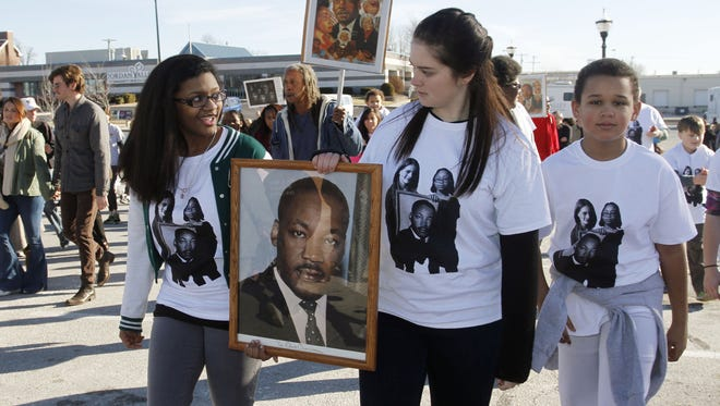In January 2015, Aubryona Marshall, left, and Kaitlin Smith carry a portrait of Martin Luther King, Jr., while walking with Payton Moore in the NAACP Martin Luther King Jr. March on Monday in Springfield. Last year, their sisters carried the photo together, and the year before that their fathers carried it.