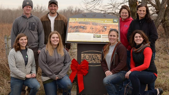 Iowa County Conservation staff and volunteers pose with the new Iowa Valley Scenic Byway sign posted along F15 Boulevard near Marengo.