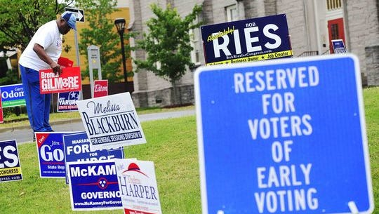 Harry Gilomore puts out signs for his wife as early voting begins at the Howard Office Building in downtown Nashville, Tenn. July 18, 2014.