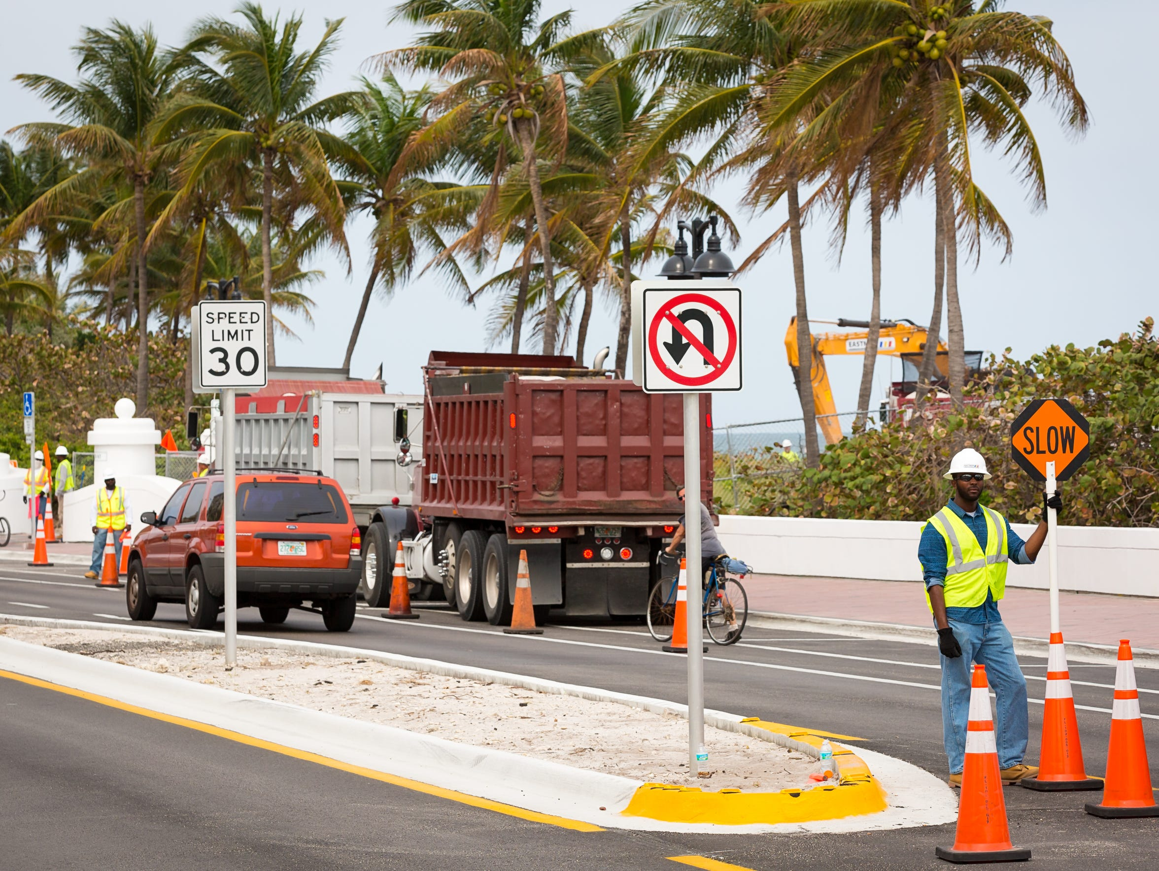Dump trucks enter a beach renourishment project along