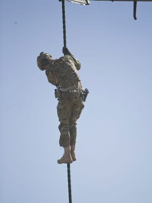 Prince Harry exiting a helicopter on fast rope during an exercise with Australia's 2 Commando Regiment in Sydney on May 7,