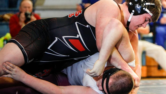 285-pounder Jake Gnegy of St. Johns prepares to stick Collin Lewis of Eaton Rapids during the Div. 2 individual wrestling district tournament at Mason February 13, 2016.