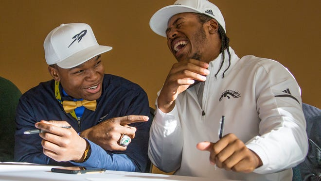 Detroit Cass Tech football players Dyontae Johnson, who is signing with Toledo, left, laughs with teammate Andre Carter, who is signing with Western Michigan during the signing day event on Wednesday, Dec. 20, 2017, at the Horatio Williams Foundation in Detroit.