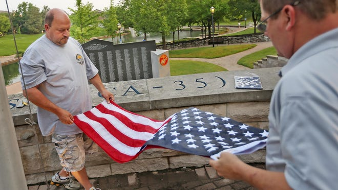 George Muncy, left, and Steve Stiegelmeyer fold a flag brought down from above the USS Indianapolis Memorial on the Canal Walk downtown, Tuesday, June 9, 2015. The Lost at Sea program is honoring sailors who died aboard the USS Indianapolis. Flags are being flown at the memorial daily for a different person. The flags are then brought down and given or sent to the family of the sailors. John Cadwallader is one of the sailors who died when the ship sank after torpedoed. Of the 1196 aboard, 900 made it into the water, but only 317 survived almost five days in the water from shark attacks, starvation, thirst, exposure and wounds. Cadwallader's family received this flag.