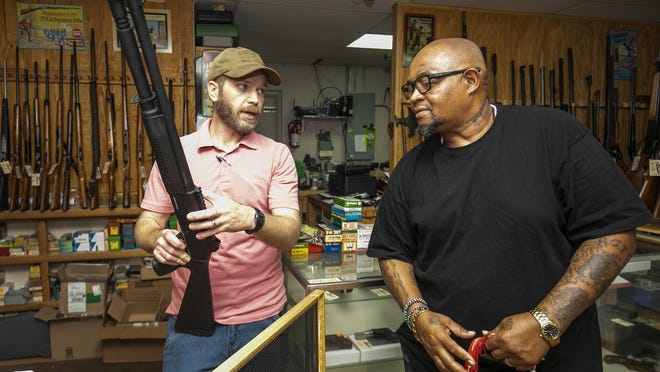 Alan Campbell, left, a salesman at Ocala Armory, explains to customer Ron Taylor that distributors across the nation don't have shotguns in stock. Taylor was shopping for a weapon for home defense.