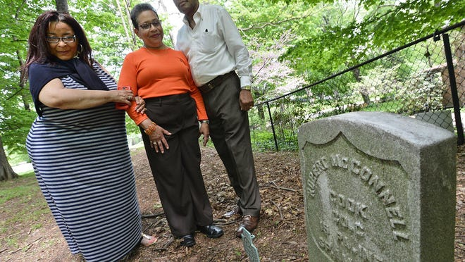 Alyse McConnell, her aunt, Mary McConnell Watson, and her brother, Timothy McConnell, from left, were photographed in May 2015 at the Gospel Hill Burial Ground in Harborcreek Township. They are descendants of Robert McConnell, whose gravestone is shown in the foreground. An earlier Robert McConnell, also an ancestor, was one of the first African-American residents of Erie County, arriving as a slave in 1794.