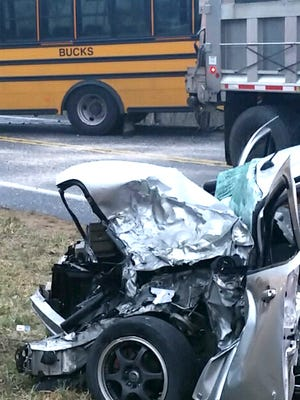 A vehicle driven by Jess Hoffer, 22, Palmrya, sits to the side of Gravel Hill Road in North Londonderry Township after it collided head-on with a school bus driven by Brooke Guber, 36, Palmyra, that was transporting students to Palmrya high school and middle school Friday morning.