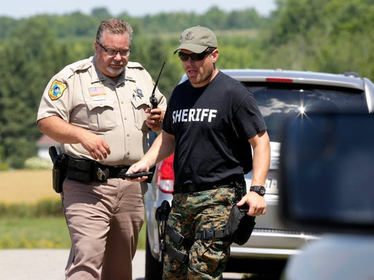 Lincoln County Sheriff department officials navigate the end of the scene where an officer involved shooting occurred early Tuesday morning in Merrill off Highway 64 on Hillview Road, July 26, 2016.