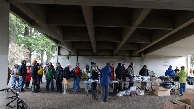 Volunteers offer food and supplies to the homeless under the Marion Street bridge in Salem in 2014.