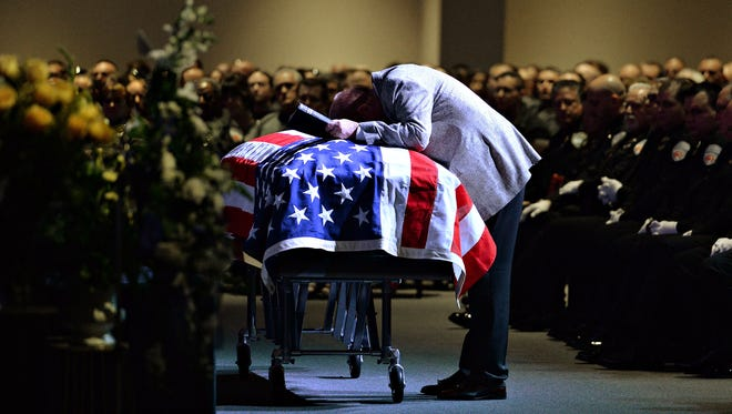 Rev. Nick Fair stops at the casket on his way to the stage at Scott Von Lanken's funeral at Rez.Church  in Loveland on Monday. Von Lanken was shot in front of Denver Union Station while working as an RTD security officer.