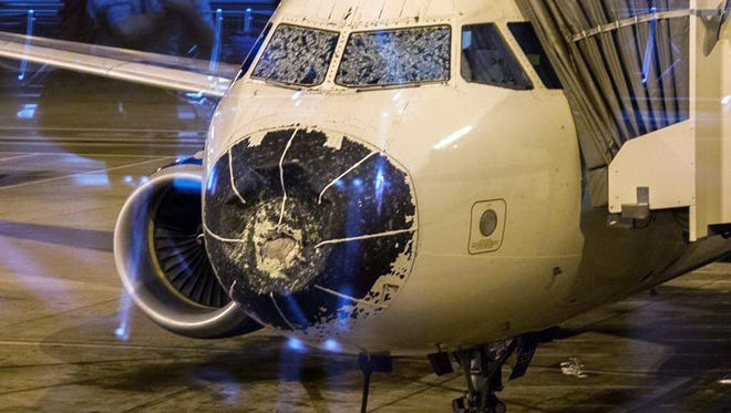 This photo provided by Beau Sorensen shows the damage done by hail to the nose cone and windshield of a Delta flight Friday, Aug. 7, 2015.