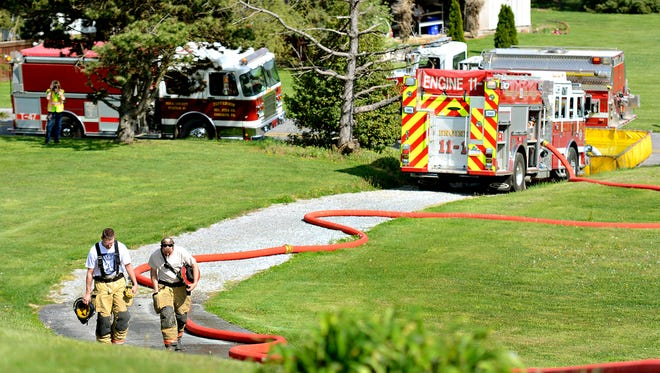 Fire crews work to salvage the trees in a wooded area behind the residence after controlling a fire at 5774 Pigeon Hill in Jackson Township, Monday, April 25, 2016. At least 10 area volunteer fire departments were on hand. Dawn J. Sagert photo