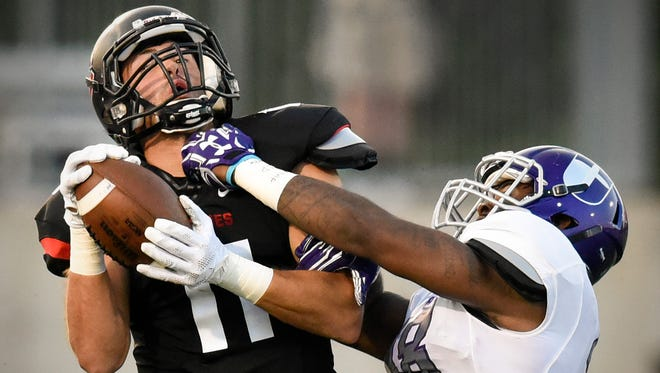 St. Cloud State wider receiver Jameson Parsons pulls in a pass while being covered by University of Sioux Falls Delvin Batiste during the second half Thursday, Sept. 1, at Husky Stadium.