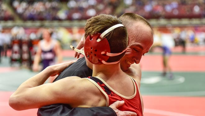 Pleasant's Carter Wolf is embraced by Coach Joe Robinson after winning a wrestling match on second day of the state wrestling tournament last year.