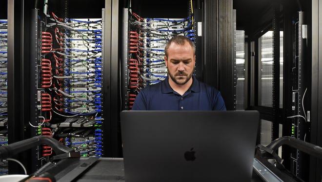 A technician updates a database on a MacBook inside Apple's Reno data center on Jan. 16, 2018.