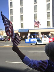 Evelyn Baggett waves several flags during the annual Veterans Day parade on Broadway Wednesday, Nov. 11, 2015, in Nashville, Tenn.
