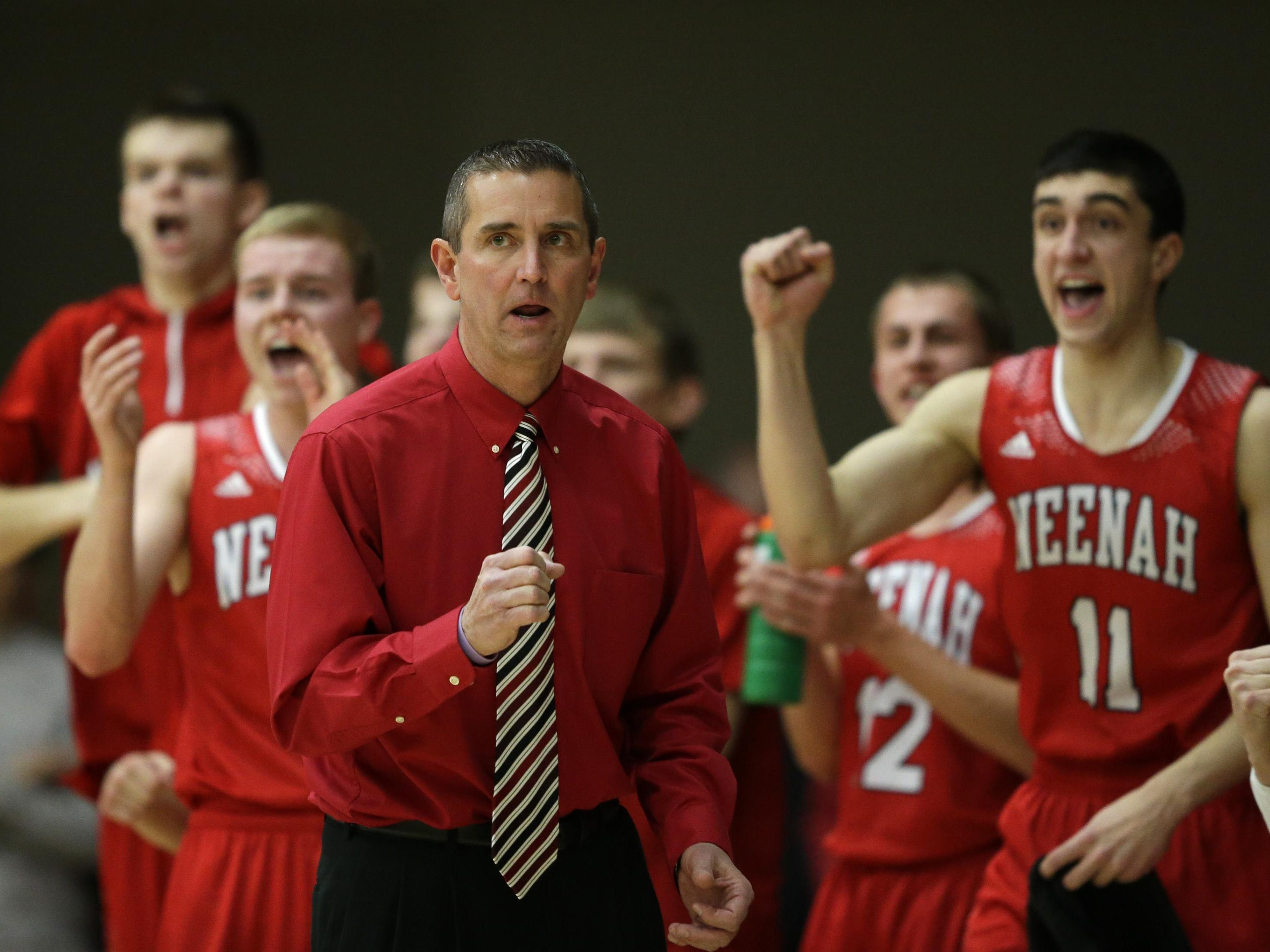 """Former Neenah boys' basketball coach Scott Bork pumps his fist after one of his players scored against Kaukauna during a Fox Valley Association game Feb. 26 in Kaukauna. Bork believes stress from coaching triggered the """"warning stroke"""" he experienced during a game last season."""