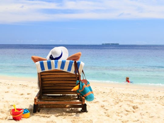 A woman sitting in a chair on a white sand beach looking out at the ocean.