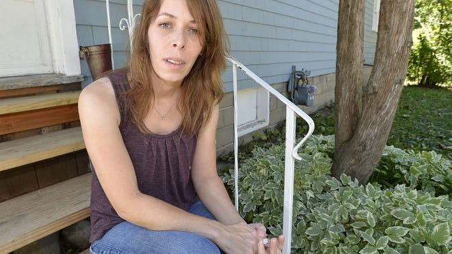 Rebekah Timlin Meddles, who contracted Lyme Disease when she was growing up in Michigan, pauses for a picture on the porch of her new home in Mount Pleasant.