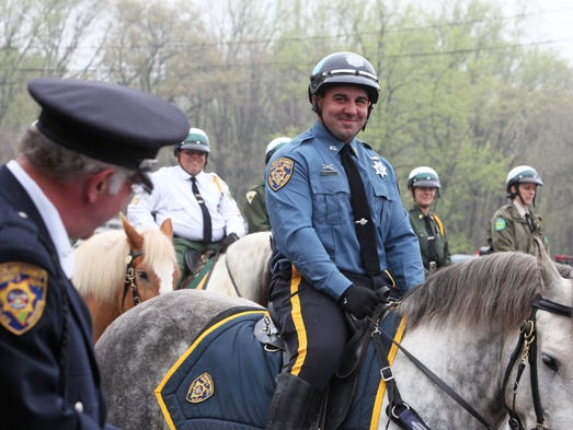 Rockland County Sheriff's Deputy Joseph Koval smiles as Deputy Carmine Romeo reads a letter from Koval's mother during the department's graduation ceremony for officers who have completed the Sheriff's 80-hour training course focusing on precision riding and application of police horses in law enforcement, May 9, 2014 in Ramapo. Deputy Koval was among two graduates to receive a special award for recognition during the training.