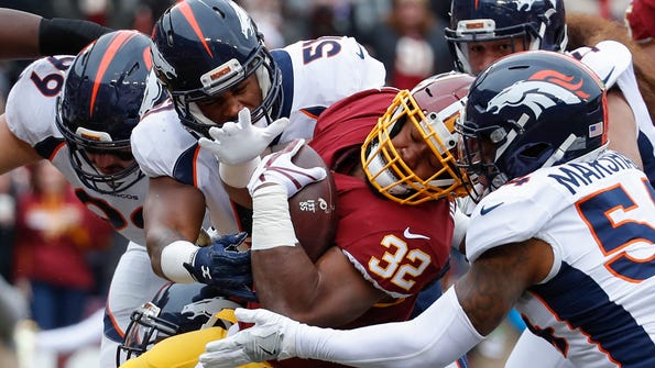 Washington Redskins running back Samaje Perine (32) tries to make headway against the Denver Broncos defense during the first half an NFL football game in Landover, Md., Sunday, Dec 24, 2017. (AP Photo/Alex Brandon)