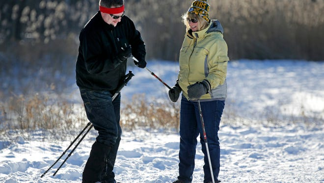 Peter Schultz offers a hand to Christina Ostrom as they head out on snowshoes at Lecker Park in Grand Chute, Wis., Saturday, January 2, 2016.Ron Page/Post-Crescent Media