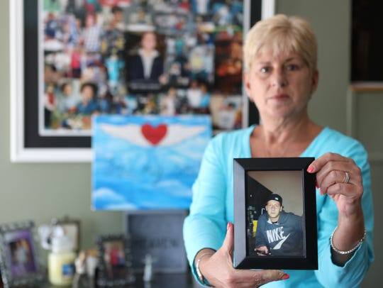 Donna Andelora, of Wayne, holds a portrait of her son,