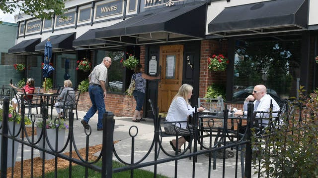 People enjoy meals in an outdoor dining area at Aunt Maude's restaurant in Ames' Main Street on Wednesday. On June 9, Mayor John Haila reached out to the Ames Chamber of Commerce, inquiring about policies the city could put in effect which would encourage more use of outdoor dining spaces during the pandemic. Photo by Nirmalendu Majumdar/Ames Tribune