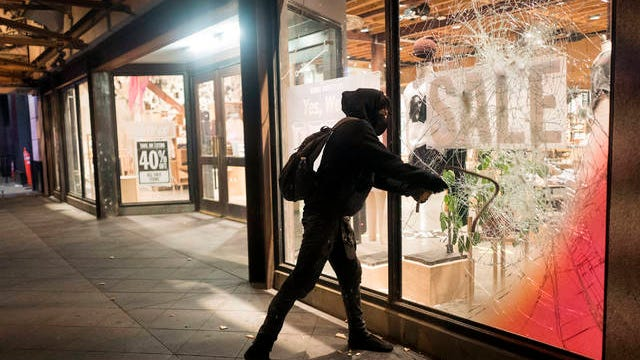 A protester breaks a window of a business during a protest over the death of George Floyd on Friday in Los Angeles. Protests have been erupting all over the country after George Floyd died earlier this week in police custody in Minneapolis.
