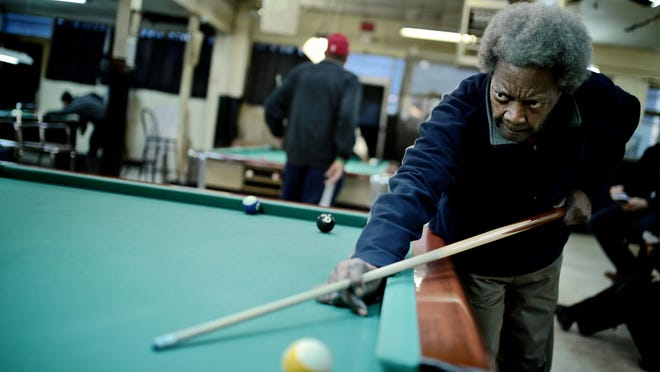 Homer Ross, 73, of Detroit, aims during a game of pool at Bill's Recreation on Feb. 5 in Detroit. Bill's is located in the shrinking wedge of what's left of the Cass Corridor, which for decades was Detroit's skid row.