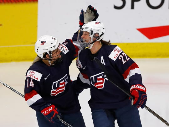 USA's Kacey Bellamy, right, celebrates a third-period goal with Brianna Decker against Canada in the gold medal game at the 2017 IIHF woman's world championship at USA Hockey Arena on April 7, 2017 in Plymouth.