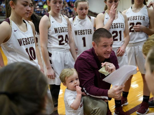 Webster Head Coach Brandon Fisher (center right) talks to his team as his son Ford Fisher (center left) holds onto him before the start of the game against the Dawson Springs Panthers in the Second Region Tournament at Webster County High School in Dixon, Ky., Monday, Feb. 26, 2018. The Trojans defeated the Panthers, 65-21, and will advance to Friday night's semifinals.