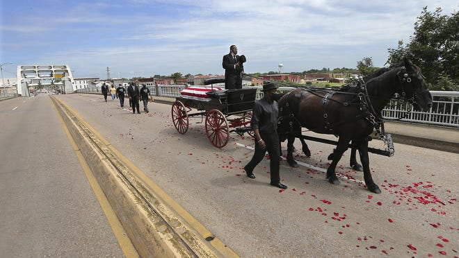 072620 Selma: The body of Rep. John Lewis makes the final crossing over the Edmund Pettus Bridge, site of the historic 1965 voting rights marches, followed by family members on Sunday, July 26, 2020 in Selma. The congressman from Georgia and civil rights icon died July 17 at age 80 after a battle with pancreatic cancer.   Curtis Compton ccompton@ajc.com