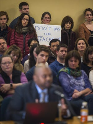 Members of the audience listen as Yaw Obeng, superintendent of the Burlington schools, makes a budget presentation as the Burlington School Board meets on April 12 to discuss possible teacher layoffs at Contois Auditorium in City Hall in Burlington.