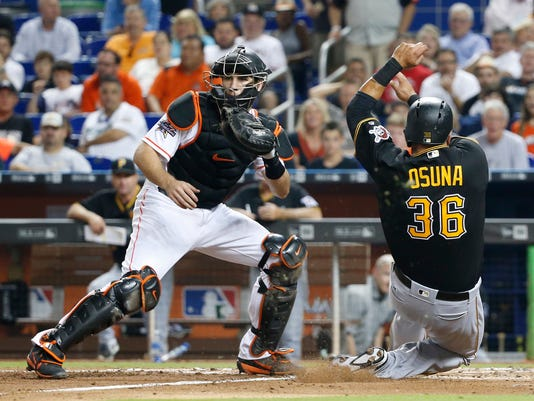 Pittsburgh Pirates' Jose Osuna (36) slides in safely to score as Miami Marlins catcher J.T. Realmuto, left, waits for the throw during the fourth inning of a baseball game, Friday, April 28, 2017, in Miami. (AP Photo/Wilfredo Lee)