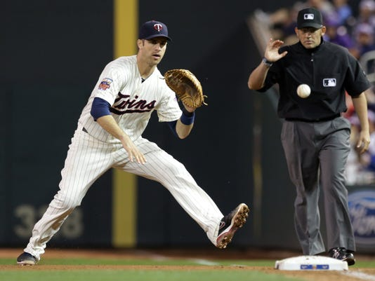 Minnesota Twins first baseman Joe Mauer fields the ball as Cleveland Indians' Jose Ramirez grounds out in the sixth inning of a baseball game, Saturday, Sept. 20, 2014, in Minneapolis. Looking on is first base umpire Manny Gonzalez. The Indians won 7-3.  (AP Photo/Jim Mone)