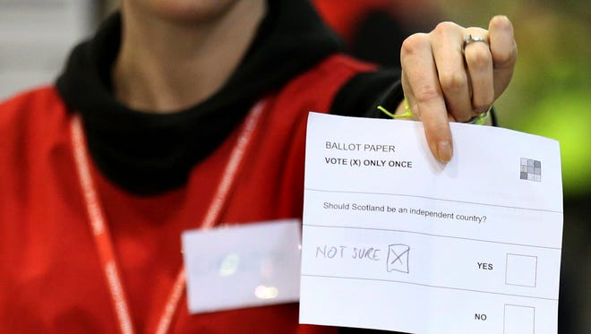 A doubtful ballot paper is held up as ballot papers are counted at the Royal Highland Centre in Edinburgh, Scotland on Sept. 18.