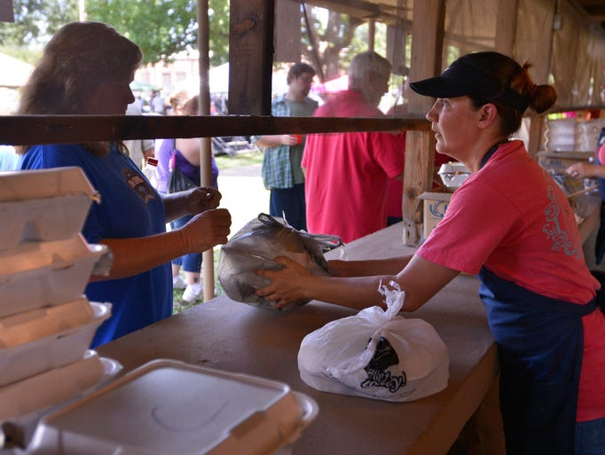 Stacie Hamm, right a first year member with the Prattville Service League, serves BBQ plates during the club's 62nd Annual BBQ on Monday, Sept. 1, 2014, at Pratt Park.