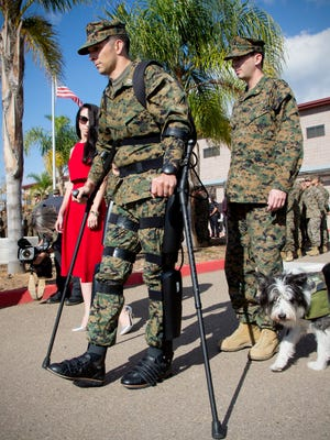 Marine Capt. Derek Herrera, along with his wife Maura and his service dog Shaggy, walks to his award and retirement ceremony at Camp Pendleton, Calif., Friday, Nov. 21, 2014.