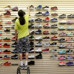 Eric Garcia arranged athletic shoes at Shaheen's Department Store, in Portland.  Shaheen's has been in business, in Portland since 1922.  May 26, 2015.