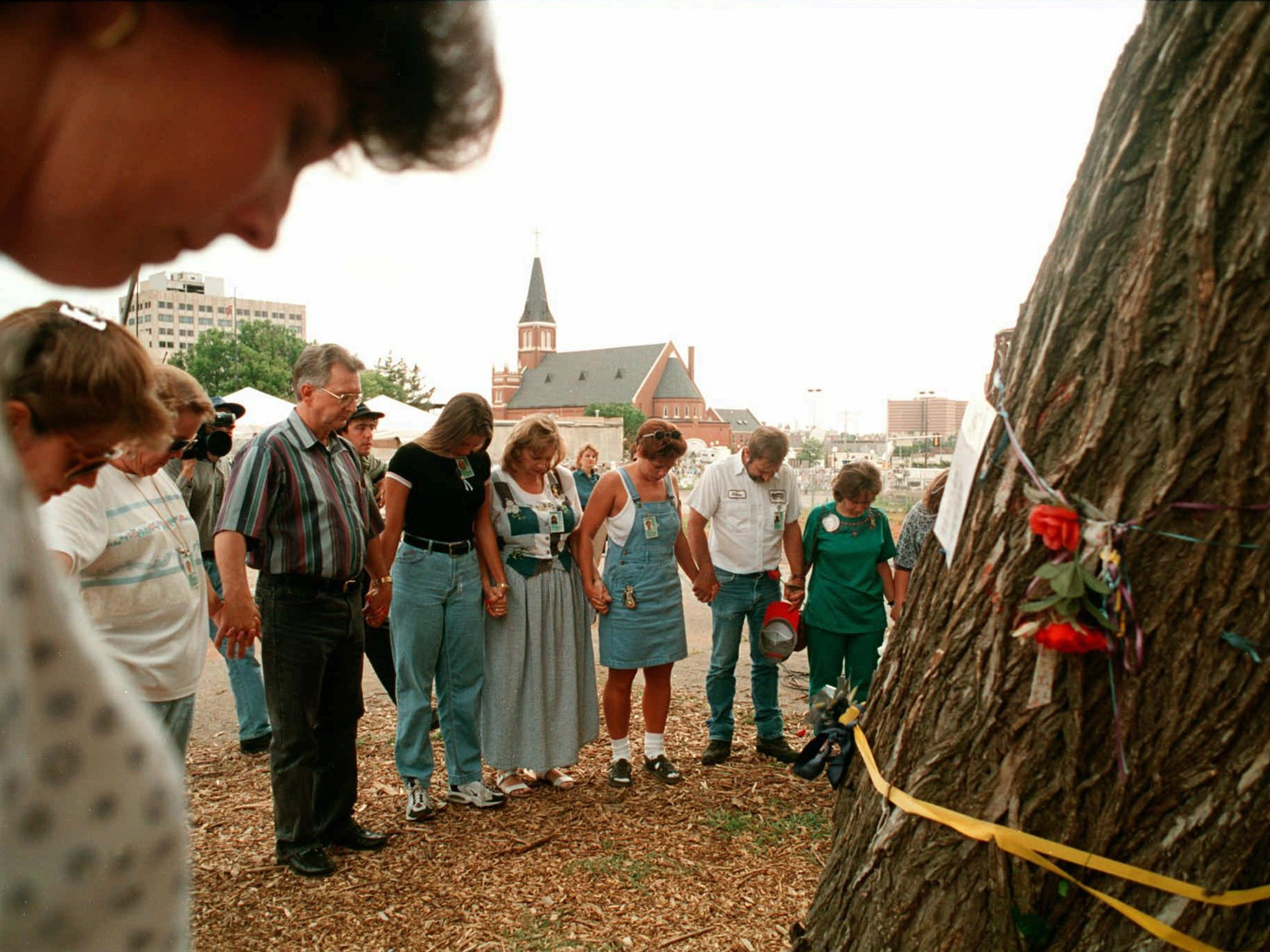 Oklahoma City bombing survivors and family members of those killed in the April 19, 1995, bombing hold hands as they form a circle around the survivor's tree after hearing the guilty verdict in the  Timothy McVeigh bombing trial on June 2, 1997.