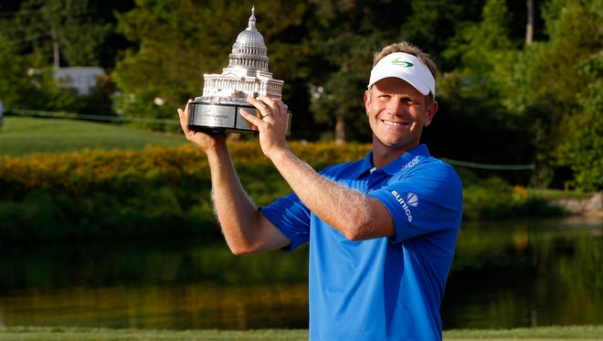 Billy Hurley III celebrates with the championship trophy after winning the Quicken Loans National golf tournament at Congressional Country Club on June 26.