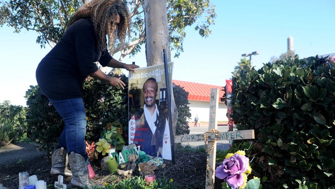 Rene Camper Stewart, of Oxnard, works on putting back together the roadside memorial in early December for her son near a bus stop on North Ventura Road in Oxnard. Her son Christopher Camper was fatally shot at the site on June 25.