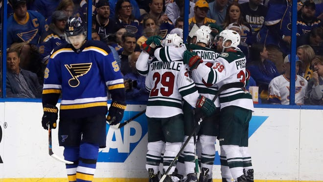 Members of the Minnesota Wild congratulate teammate Martin Hanzal, of the Czech Republic, on his goal as St. Louis Blues' Magnus Paajarvi, left, of Sweden, skates past during the second period in Game 4 of an NHL hockey first-round playoff series Wednesday, April 19, 2017, in St. Louis.