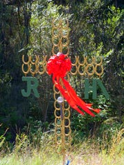The family of James Hiles Jr. changes the decoration on the cross of horseshoes that marks the spot of his fatal accident every couple of months and each holiday season.