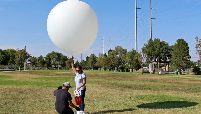 New Mexico State University environmental science undergraduate student Octavio Nayares, left, and environmental science graduate student Zahra Ghodsi Zadeh prepare to launch a weather balloon with an ozone level sensor attached. NMSU faculty and students are launching the weather balloons as part of a project with the El Paso Metropolitan Planning Organization and Texas Commission on Environmental Quality.
