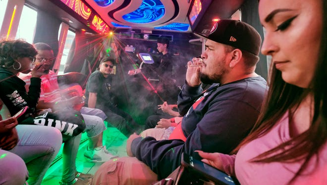 In this May 19, 2018 photo tourists smoke cannabis on the Green Line Trips bus tour in Los Angeles. Recreational marijuana sales became legal in California this year, and the industry is targeting tourists as well as locals, with tours, shops, lodging and ads. And there are cannabis bus tours, too, like Green Line Trips, with stops at local pot dispensaries and Griffith Park or Santa Monica.