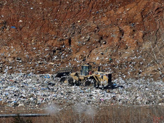A tractor moves garbage around at Middle Point Landfill in Walter Hill