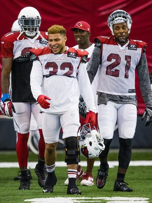 Arizona Cardinals players Antonio Cromartie (left), Tyrann Mathieu (center) and Patrick Peterson walk between drills during practice inside the bubble at the Tempe practice facility on Sept. 4, 2014.