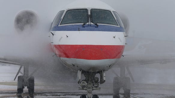 An American Airlines jet is sprayed down in an anti-icing